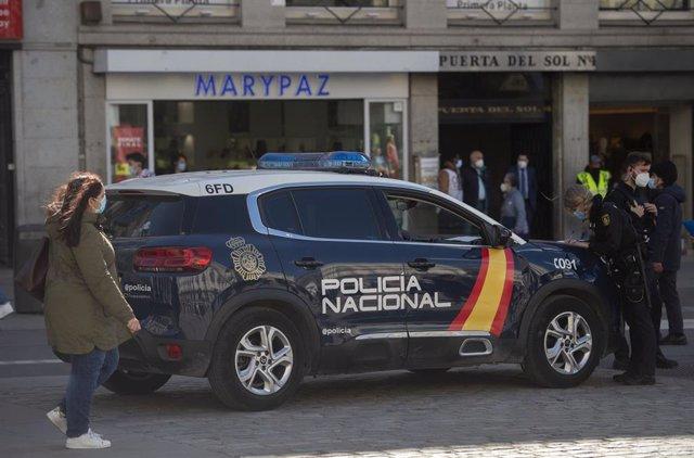 Archivo - Un coche de Policía Nacional circula por la Puerta del Sol, Madrid