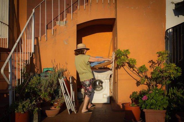 Una mujer ante una lavadora en una terraza