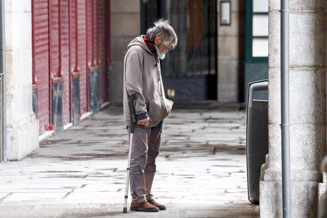 Archivo - Un hombre sin hogar camina por los soportales de la Plaza Mayor durante el primer día de la cuarta semana de estado de alarma decretado por el Gobierno para combatir el coronavirus, en Madrid (España) a 6 de abril de 2020.