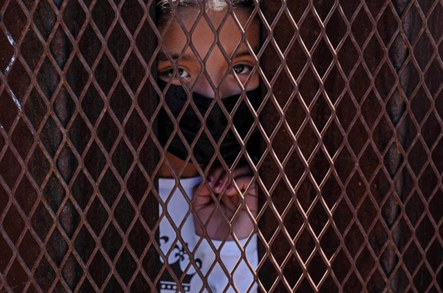 Archivo - 30 April 2021, US, Nogales: A young asylum-seeking migrant stands behind the fence at border wall separating the United States and Mexico. Photo: Christopher Brown/ZUMA Wire/dpa