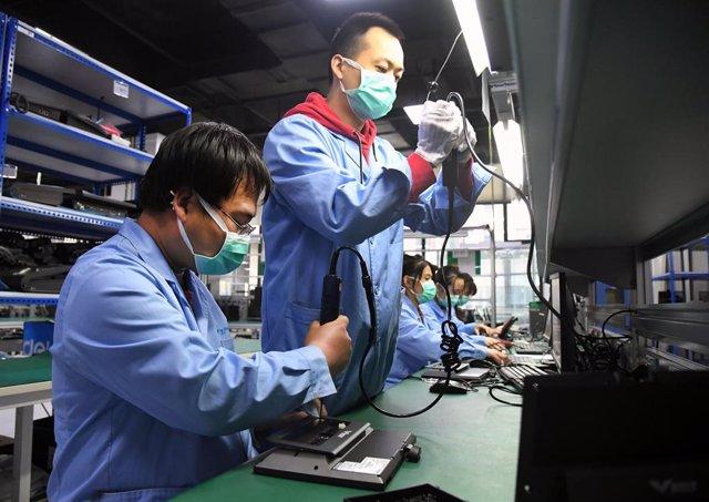 Archivo - Un grupo de trabajadores durante su turno en una fábrica de Pekín que se encarga de reparaciones electrónicas.