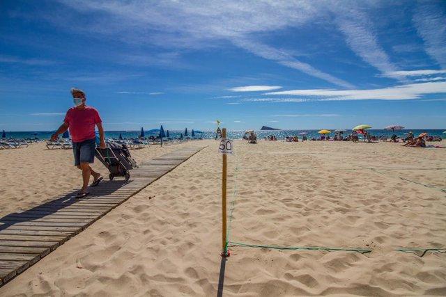 Archivo - Un hombre camina por la pasarela de la Playa de Levante de Benidorm durante el Día Mundial del Turismo 2020, en Benidorm, Alicante, Comunidad Valenciana (España) a 27 de septiembre de 2020. Esta edición, bajo el lema de 'Turismo y desarrollo rur