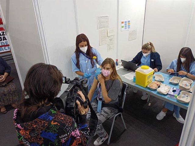 Una joven menor de 50 años recibe la primera vacuna en el Pabellón La Casilla de Bilbao.