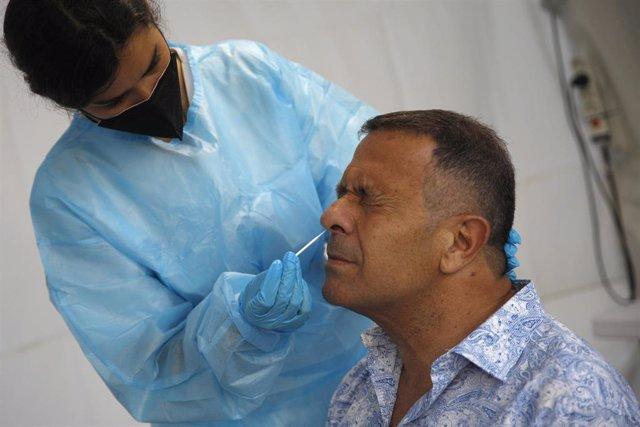 Un sanitario hace un test de antígenos en Can Milà a un hombre que va a participar en un ensayo sobre coronavirus en bares musicales, a 20 de mayo de 2021, en Barcelona, Catalunya (España). Las personas que acceden a estas pruebas participarán posteriorme