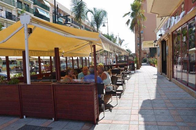 Archivo - Unos turistas aprovechan los últimos días del verano para tomarse un aperitivo en una terraza de Fuengirola.