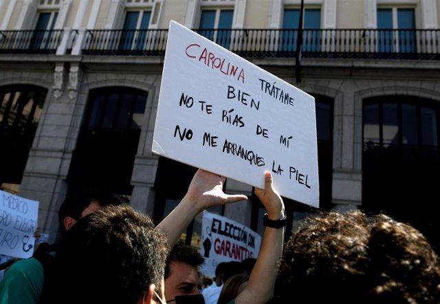 Persona sujetando y levantando una pancarta frente a la Puerta del Sol para exigir una elección de plazas con garantías el 8 de junio de 2021, en Madrid (España). Organizada por la Confederación Estatal Sindicatos Médicos (CESM), con esta nueva protesta,