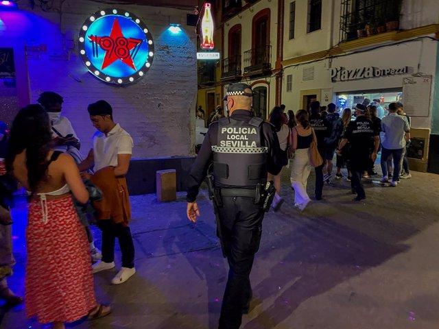 Arxiu - Un policia municipal de Sevilla demana a un jove que es posi la mascareta a la sortida d'una discoteca.