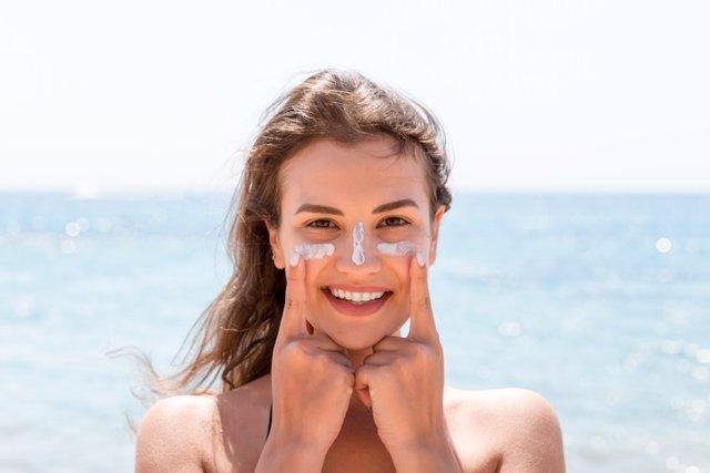 Archivo - Mujer al sol, crema solar en la cara.