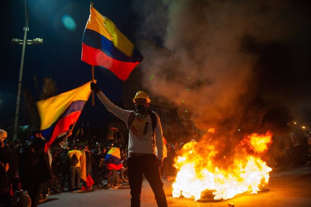 12 May 2021, Colombia, Bogota: A demonstrator waves a Colombian flag in front of burnt tires during a protest against the government of Colombian President Ivan Duque Marquez. Photo: Chepa Beltran/LongVisual via ZUMA Wire/dpa