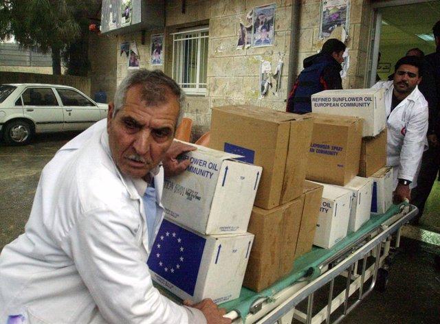 Archivo - Médicos palestinos ayudan a descargar una entrega de alimentos y suministros de emergencia de la ONU en un hospital de Ramala en Cisjordania.