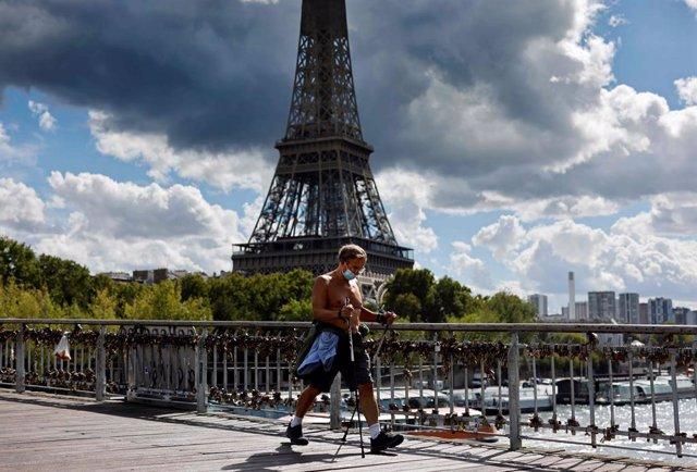Archivo - Un hombre hace ejericico junto a la Torre Eiffel en París.