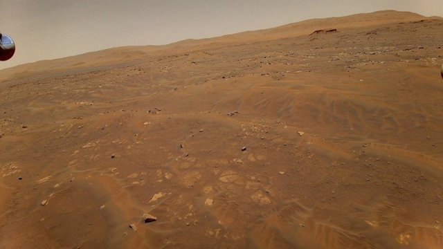 Esta imagen mirando hacia el oeste, hacia la unidad geológica Séítah en Marte, fue tomada desde una altura de 10 metros (33 pies) por el helicóptero Ingenuity Mars de la NASA durante su sexto vuelo, el 22 de mayo de 2021.