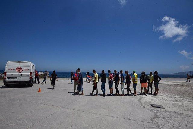 Varios migrantes, que entraron a Ceuta hace 3 semanas hacen cola para recibir alimentos de Cáritas Diocesana, a 7 de junio de 2021, en Ceuta, (España).