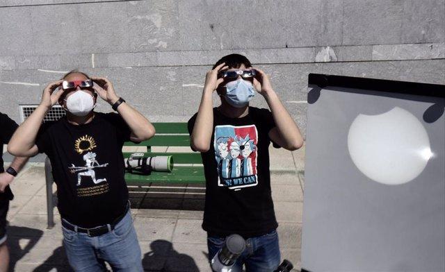 Dos personas contemplan en el exterior del planetario de Pamplona el eclipse solar parcial que se puede apreciar también proyectado en una superficie blanca, a 10 de junio de 2021.