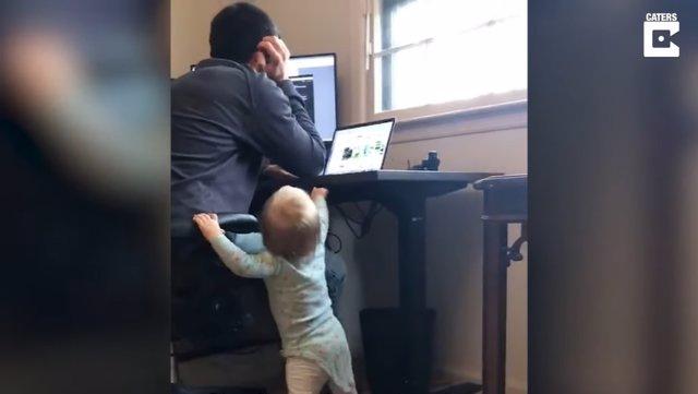 Esta niña de 15 meses cambiando la altura del escritorio de su padre mientras trabaja es un divertido resumen del teletrabajo en pandemia