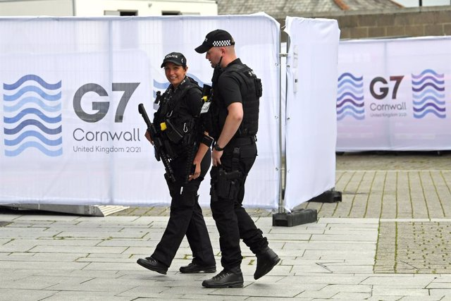 10 June 2021, United Kingdom, Falmouth: Police officers walk through Falmouth's media centre ahead of the G7 summit in Cornwall, which will be held from 11 to 13 June. Photo: Stefan Rousseau/PA Wire/dpa
