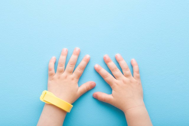 Archivo - Yellow mosquito repellent band on baby wrist on light blue table background. Pastel color. Closeup. Point of view shot. Protection from insects. Top down view.