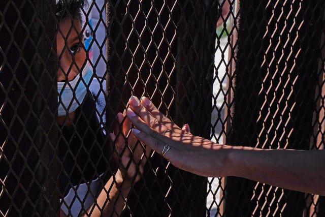 Archivo - Un niño solicitante de asilo toca la valla que separa México de Estados Unidos en Nogales.