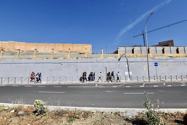 Varios migrantes procedentes de Marruecos hacen cola en las puertas de la frontera de Ceuta donde agentes de la Policía Nacional reparten citas para solicitud de asilo, a 2 de junio de 2021, en Ceuta (España).