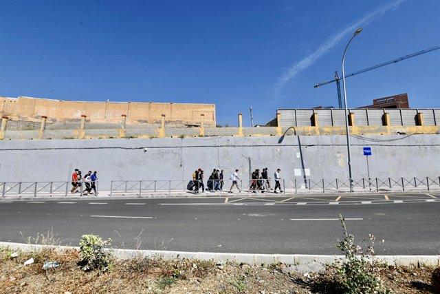 Diversos migrants procedents del Marroc fan cua en les portes de la frontera de Ceuta on agents de la Policia Nacional reparteixen cites per a sol·licitud d'asil, a 2 de juny de 2021, a Ceuta (Espanya).