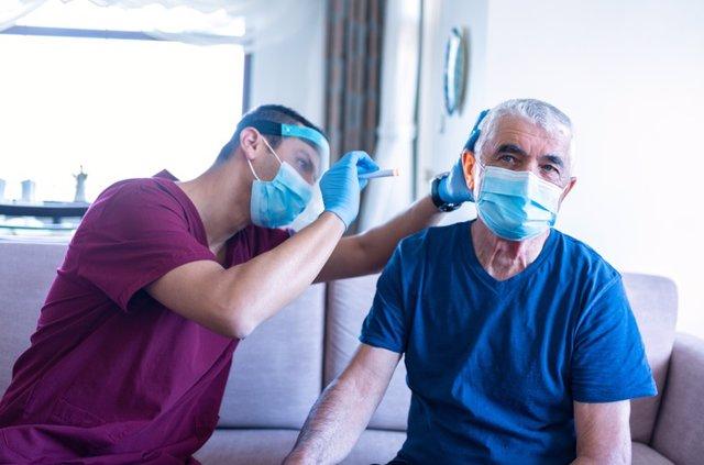 Archivo - El trabajador sanitario masculino examina el oído del anciano en su casa durante la epidemia de coronavirus.