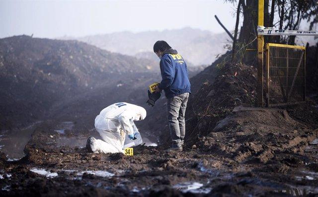 Archivo - Investigadores forenses recogen muestras entre las cenizas después de que varios camiones fueran incendiados en Chile.