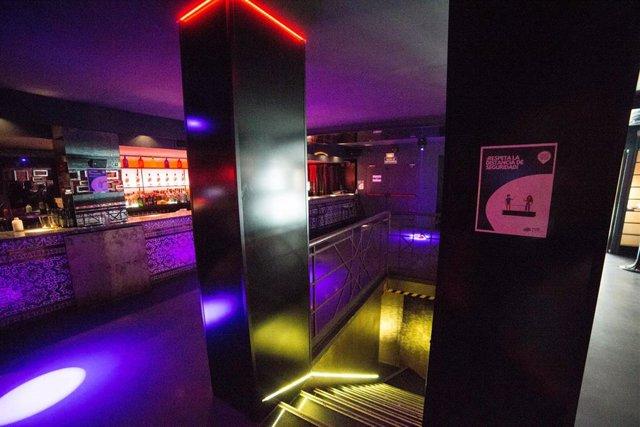 Archivo - Carteles que recuerdan la necesidad de mantener la distancia de seguridad en una discoteca de Madrid.