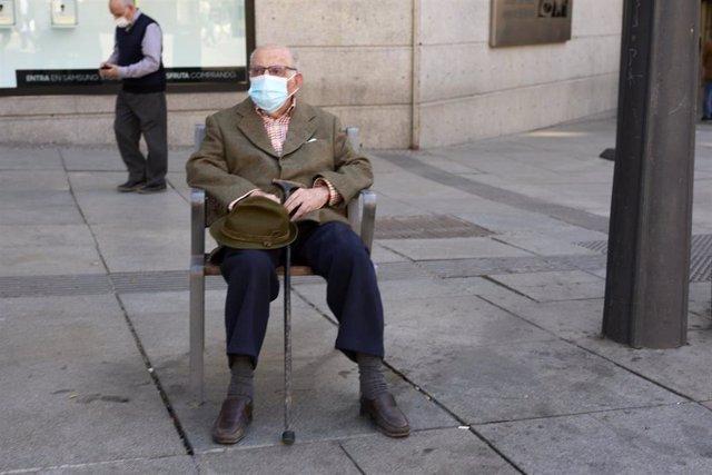 Archivo - Un anciano sentado en un banco de la Puerta del Sol con mascarilla, a 7 de mayo de 2021, en Madrid (España). A partir del domingo 9 de mayo no habrá toque de queda en Madrid, y se permitirán las reuniones en domicilios. Sin embargo, se mantendrá