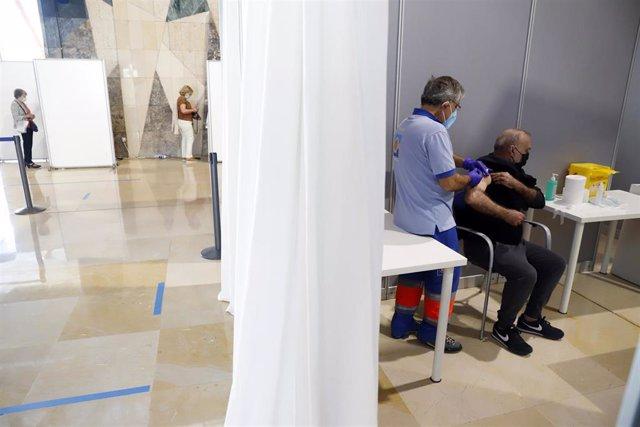 Archivo - Imagen de archivo de varias personas asisten a la vacunación masima en el Palacio de Ferias y Congresos de la capital