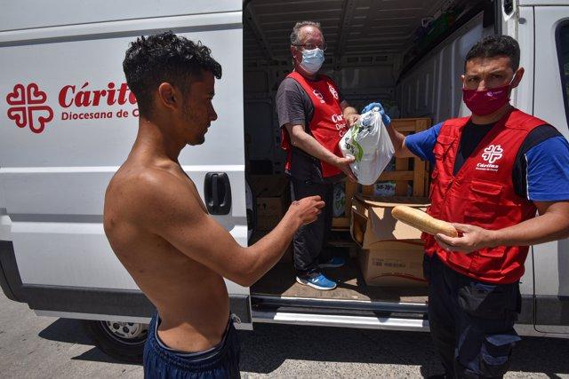 Trabajadores de Cáritas Diocesana reparten alimentos a migrantes que entraron a Ceuta hace 3 semanas, a 7 de junio de 2021, en Ceuta, (España).