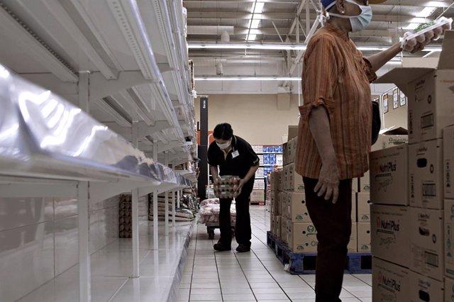 Archivo - Trabajador de un supermercado en Malasia durante el bloqueo nacional por coronavirus, en marzo de 2020