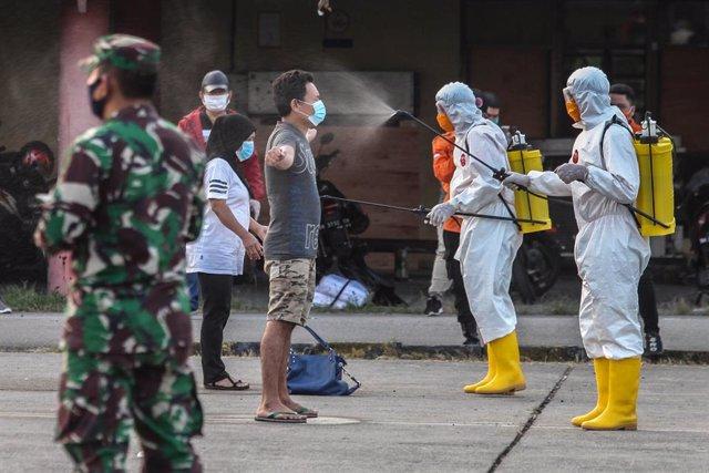 Archivo - Imagen de archivo de trabajadores sanitarios desinfectando a un hombre en Indonesia.