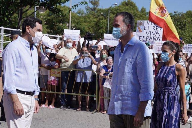 Archivo - El presidente de la Junta de Andalucía, Juanma Moreno, saluda a los reyes Felipe VI y doña Letizia en Sevilla (Foto de archivo).