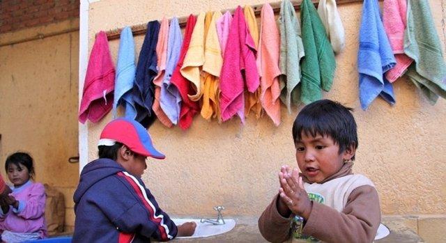 Archivo - Dos niños en Bolivia se lavan las manos en una estación apoyada por UNICEF.