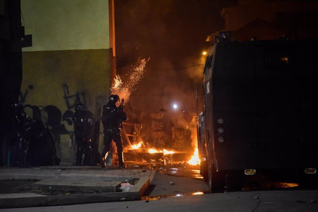 28 May 2021, Colombia, Pasto: A riot police officer shoots a tear gas canister during clashes with demonstrators following a protest against the government of President Ivan Duque Marquez. Colombian President Ivan Duque on Friday night said military assis