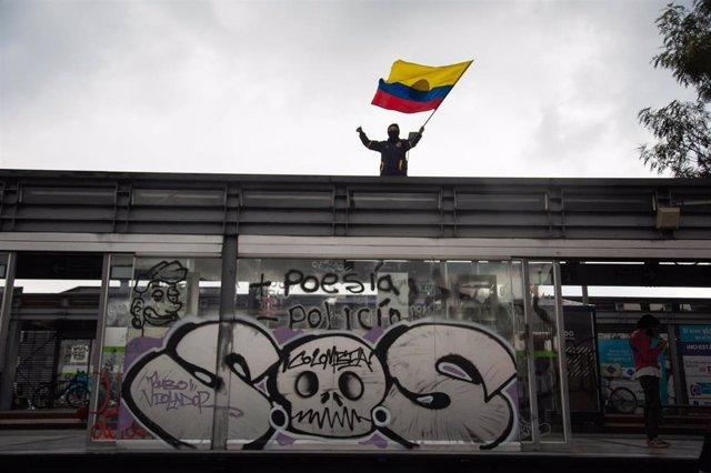 Un hombre ondea una bandera de Colombia