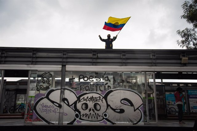"""28 May 2021, Colombia, Bogota: A demonstrator waves a Colombian flag over a transmilenio bus stop that reads """"S.O.S Colombia"""" during a protest against the government of President Ivan Duque Marquez. Colombian President Ivan Duque on Friday night said mili"""