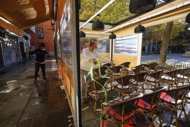 Archivo - Camareros limpiando y poniendo las mesas en las terrazas de los bares a primera hora de la mañana en Granada en una imagen de archivo