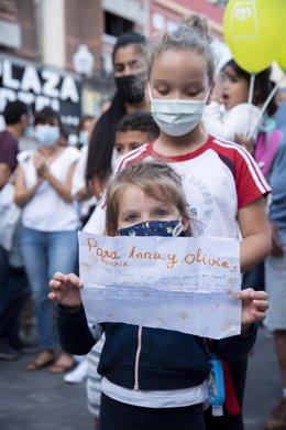 """Dos niñas con un cartel, en homenaje a Anna y Olivia, participan en una concentración feminista en la Plaza de la Candelaria en repulsa por """"todos los feminicidios"""", a 11 de junio de 2021, en Santa Cruz de Tenerife, Tenerife, Islas Canarias (España)."""