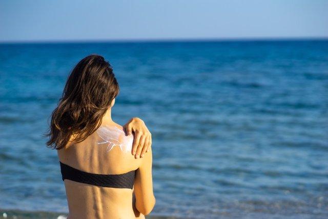 Archivo - Mujer joven aplicando crema solar en la espalda.