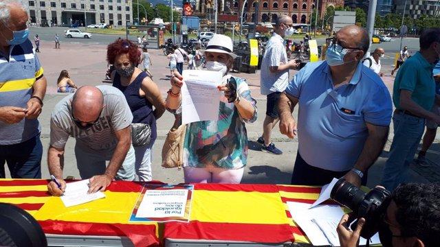 Algunes persones signen contra els indults en la taula instal·lada pel PP a la plaça Espanya de Barcelona.