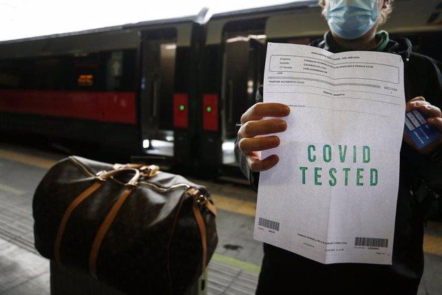 Archivo - Un home amb un certificat negatiu per coronavirus en una estació de tren a Roma.