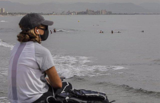 Archivo - Una mujer protegida con mascarilla en la Playa de la Malvarros