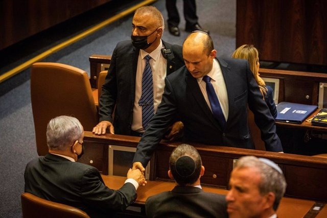 El primer ministro israelí, Naftali Bennett, da la mano al primer ministro saliente, Benjamin Netanyahu, en la Knesset