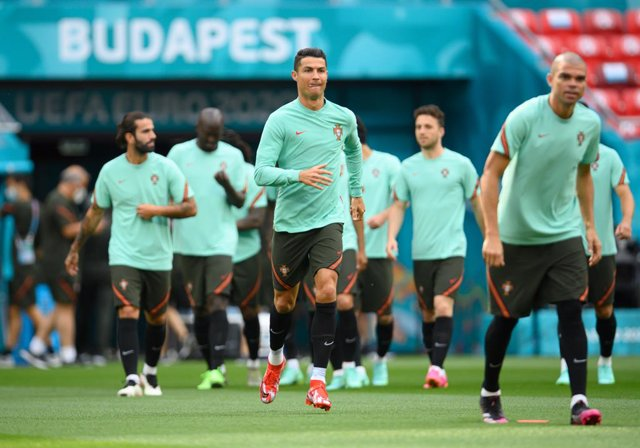 14 June 2021, Hungary, Budapest: Portugal's Cristiano Ronaldo (C) walks onto the pitch at the start of a training session for the team at the Puskas Arena ahead of Tuesday's UEFAEURO2020 Group F soccer match against Hungary. Photo: Robert Michael/dpa-Ze