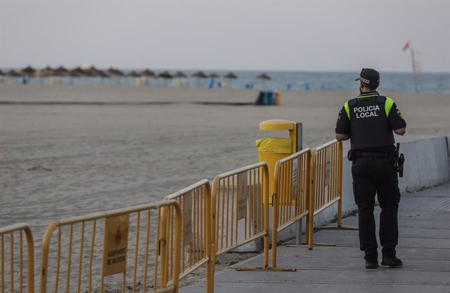 Archivo - Arxiu - Un policia local fa guàrdia en la platja de la Malva-rosa durant la nit de Sant Joan