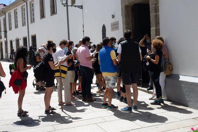 Archivo - Peregrinos con mascarillas esperando su turno para entrar en el albergue