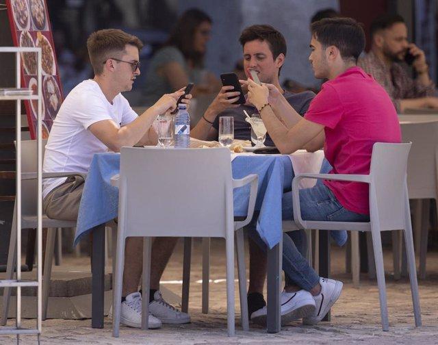 Tres hombres comen en una terraza del centro de la capital.