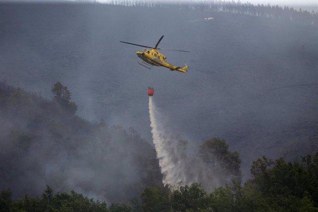 Labores de extinción del incendio forestal que se originó la pasada madrugada en el entorno de la localidad de Ferreirós de Abaixo, en el municipio de Folgoso do Courel, a 12 de junio de 2021, en Lugo, Galicia (España). El incendio forestal ha quemado una