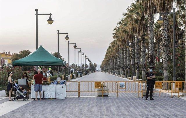 Archivo - Un policía local hace guardia en la playa de la Malvarrosa durante la noche de San Juan